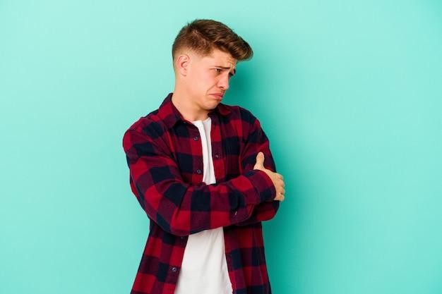 반복적 인 작업에 지친 파란색 벽에 고립 된 젊은 남자