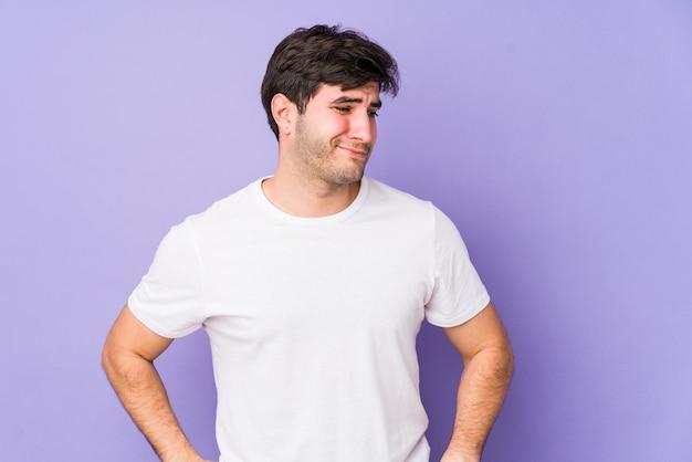 Молодой человек, изолированный на фиолетовом, смущен, чувствует себя сомнительным и неуверенным.