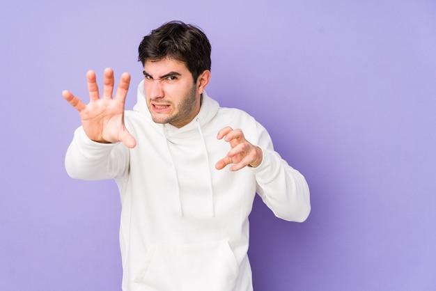 猫を模倣した爪、攻撃的なジェスチャーを示す紫色で孤立した若い男。