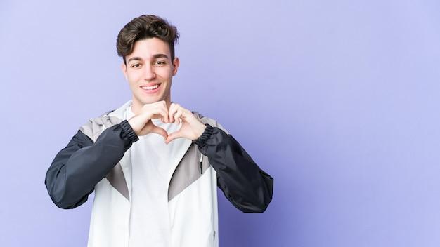 笑顔と手でハートの形を示す紫色の壁に孤立した若い男