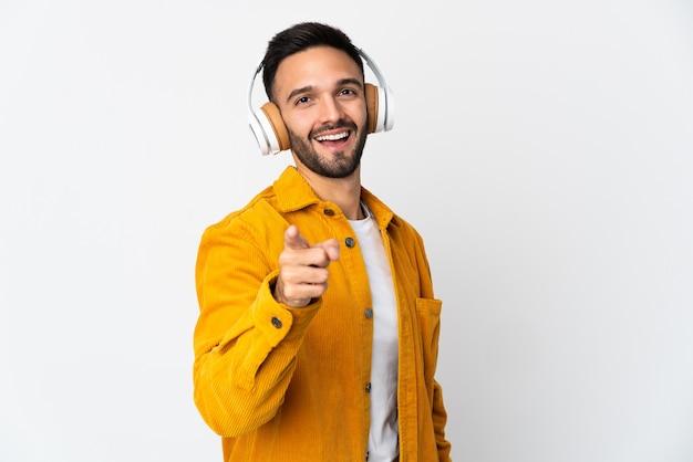 Молодой человек, изолированные на белом фоне, слушает музыку