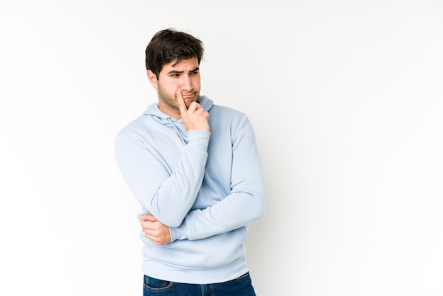 Молодой человек изолирован на белом, глядя в сторону с сомнительным и скептическим выражением лица.