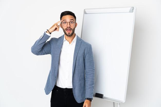 ホワイトボードでプレゼンテーションを行い、解決策を実現しようとしている白い壁に孤立した若い男