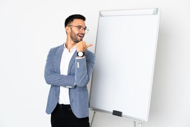 ホワイトボードにプレゼンテーションをし、側面を指している白い壁に孤立した若い男