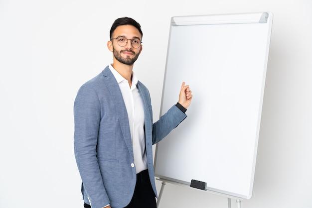 ホワイトボードでプレゼンテーションを行う白い壁に孤立した若い男