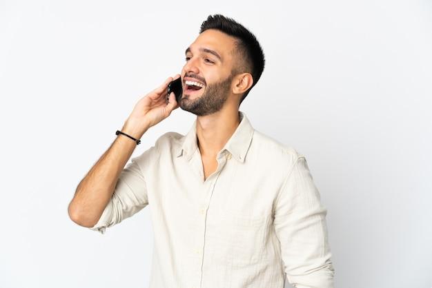 Молодой человек изолирован на белой стене, разговаривая с кем-то по мобильному телефону