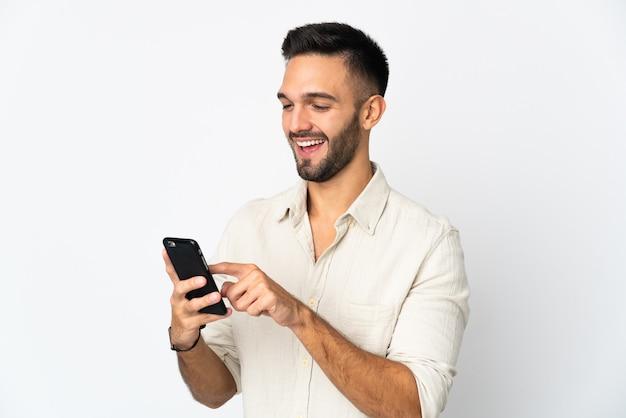 Молодой человек изолирован на белой стене, отправляя сообщение или электронное письмо с мобильного телефона