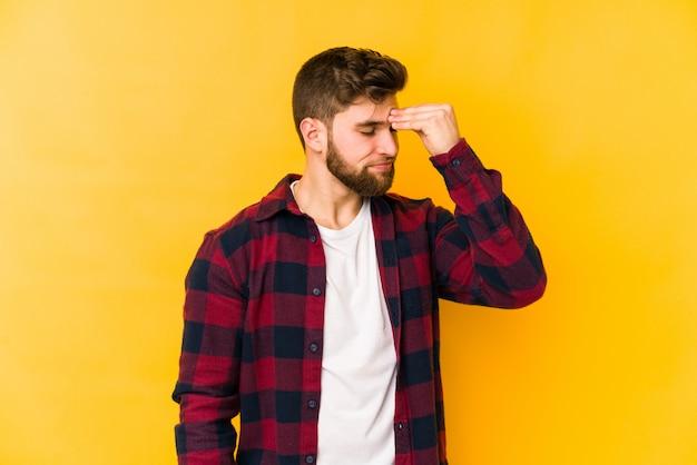 顔の前に触れる頭の痛みを持っている黄色の壁に分離された若い男