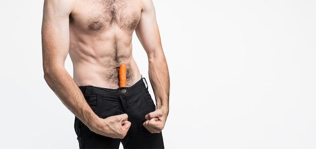 배경 위에 절연 젊은 남자. 남자의 사진은 그의 바지에 당근이 있고 그가 성적이고 강력하다는 것을 보여줍니다. 잘 만들어진 튼튼한 몸. 창백한 피부