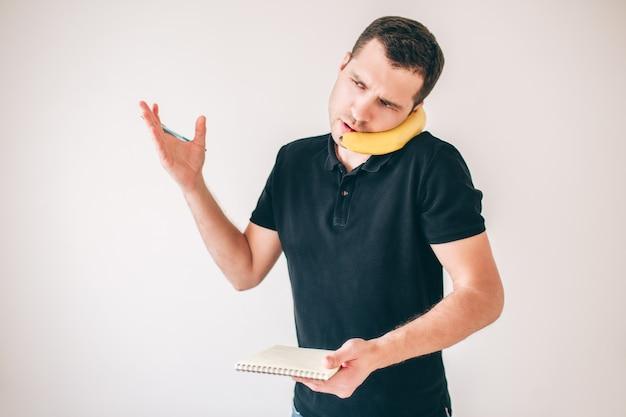 若い男が白で隔離されました。スマートフォンとしてバナナを使用して話している忙しい深刻な男。ノートを手に持って説明します。カジュアルなビジネスマン。