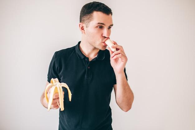 젊은이 화이트 이상 격리입니다. 기쁨으로 바나나를 먹는 사람. 서로 다른 손에 두 개의 분리 된 부분을 잡습니다.