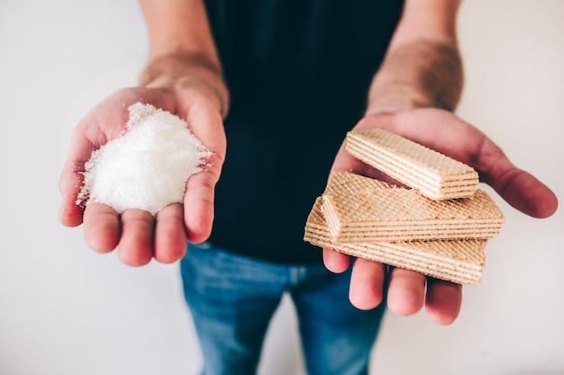 Молодой человек изолированный над белизной. парень держит кристаллический сахар в одной руке и вафли в другой. сладкая пища для нездорового ухода и проблем со здоровьем.