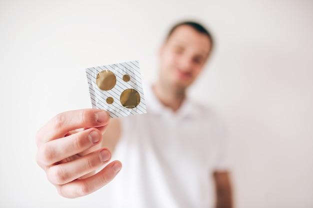흰 벽에 고립 된 젊은 남자. 콘돔을 손에 들고 흐리게 defocused 남자입니다.