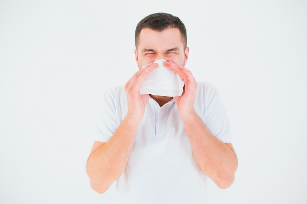 Молодой человек изолированный над белой стеной. покройте нос белой тканью. больной и больной человек чихает в белую салфетку.