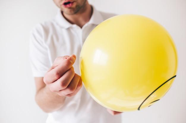 흰 벽에 고립 된 젊은 남자. 보기를 잘라 바늘을 손에 들고 노란색 풍선을 피어 싱 준비가 남자의 닫습니다.