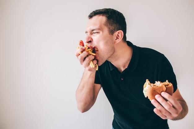 Молодой человек изолированный над белой стеной. обжора парень, пожирающий картофель фри, который держится в руке. укушенный гамбургер в другом. вкусная вкусная закуска или еда еды.