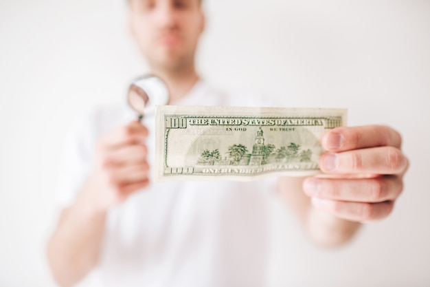 若い男が白い壁に分離されました。男は100ドル札を手にして、虫眼鏡でそれを見てください。ぼやけた壁。