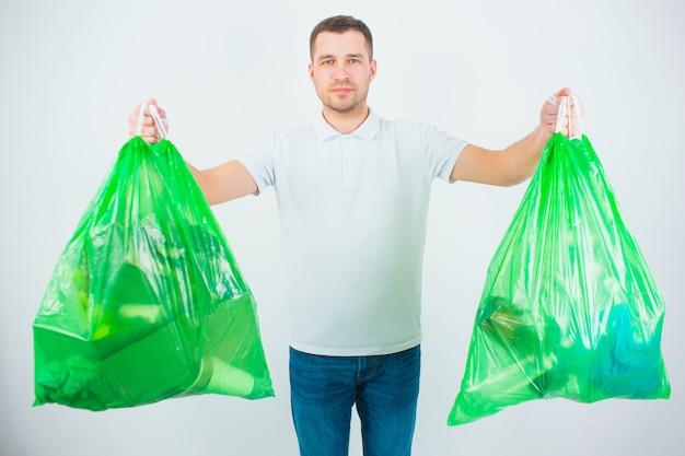 흰 벽에 고립 된 젊은 남자. 남자는 쓰레기와 쓰레기가 담긴 비닐 봉지를 두 개 가지고 있습니다.