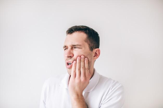 Молодой человек изолированный над белой стеной. парень страдает от зубной боли и боли. нужен уход за полостью рта и лечение. держи руку на щеке.