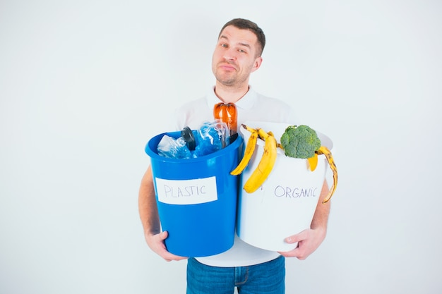 흰 벽에 고립 된 젊은 남자. 행복한 성인 남자는 유기 및 플라스틱 폐기물로 두 개의 분리 된 양동이를 개최합니다. 깨끗하고 건강한 환경 관리.