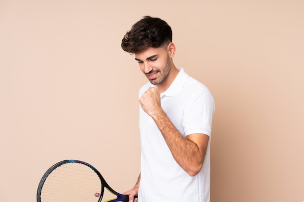 Young man over isolated playing tennis and celebrating a victory
