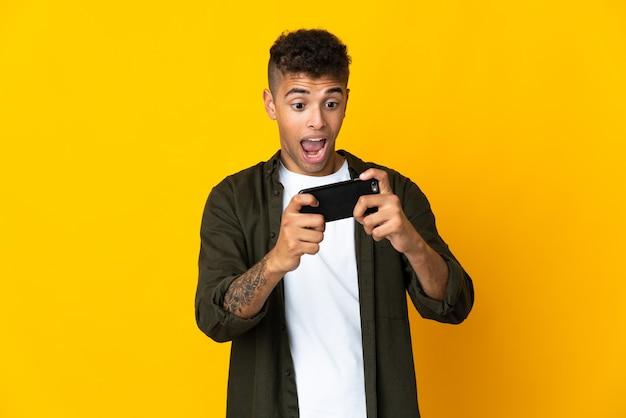 Молодой человек изолирован, играя с мобильным телефоном
