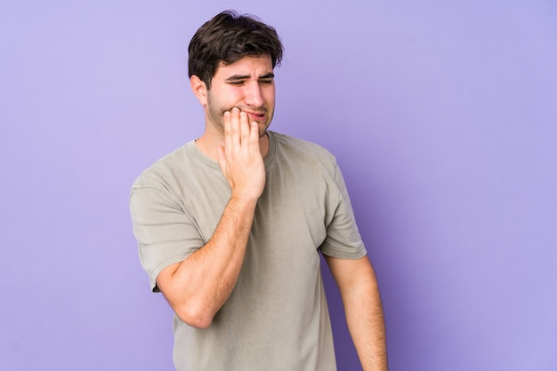 Young man isolated on purple having a strong teeth pain, molar ache.