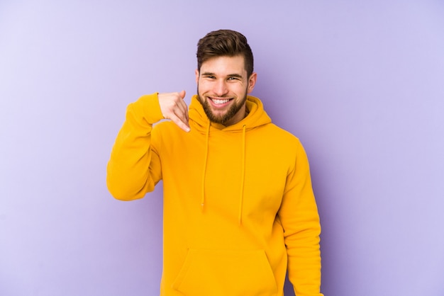 Young man isolated on purple laughing about something, covering mouth with hands.