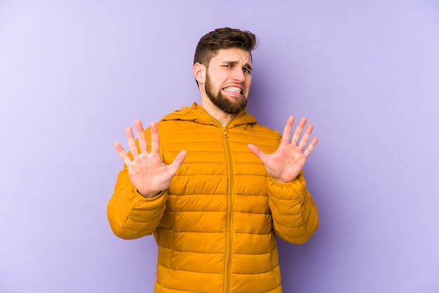 Young man isolated on purple rejecting someone showing a gesture of disgust.