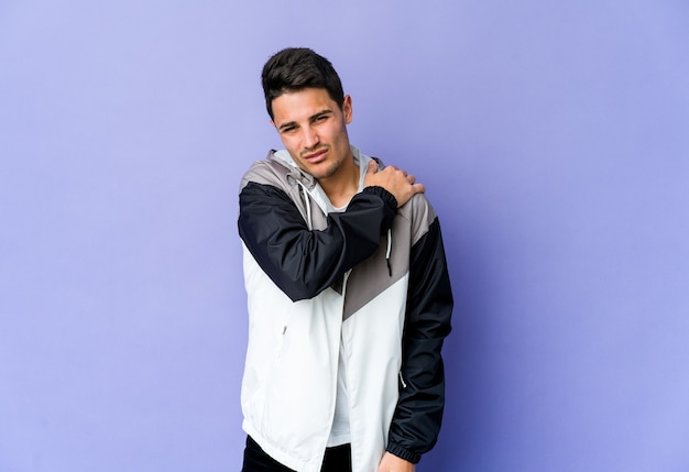 Young man isolated on purple wall having a shoulder pain