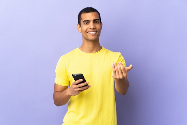 Young man over isolated purple wall using mobile phone inviting to come