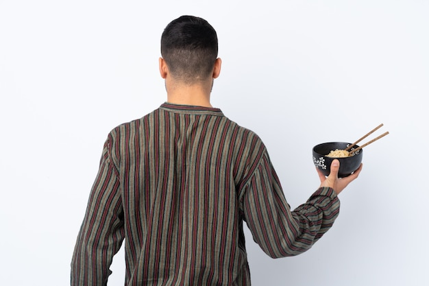 Young man over isolated wall in back position while holding a bowl of noodles with chopsticks