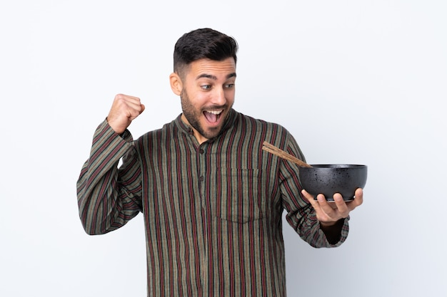 Young man over isolated wall celebrating a victory while holding a bowl of noodles with chopsticks