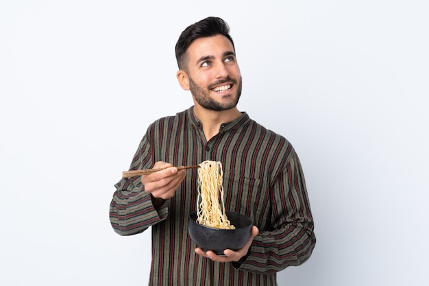 Young man over isolated wall holding a bowl of noodles with chopsticks and looking up
