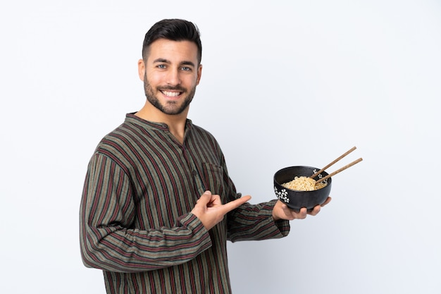 Young man over isolated wall and pointing it while holding a bowl of noodles with chopsticks