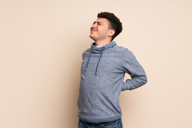 Young man over isolated wall suffering from backache for having made an effort