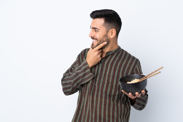 Young man over isolated wall thinking an idea and looking side while holding a bowl of noodles with chopsticks