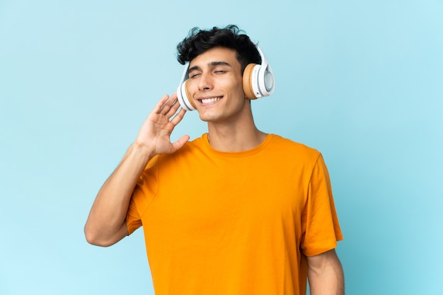 Young man isolated on white background listening music