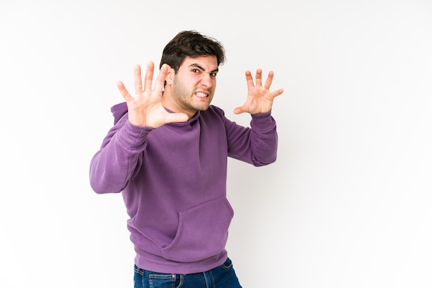 Young man isolated on white background upset screaming with tense hands.