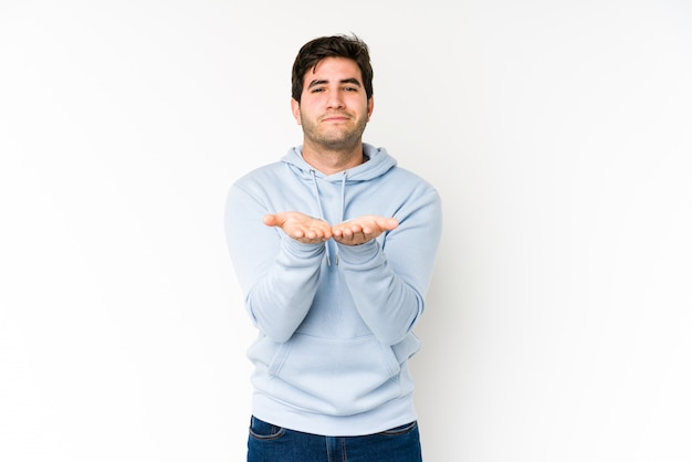 Young man isolated on white holding something with palms