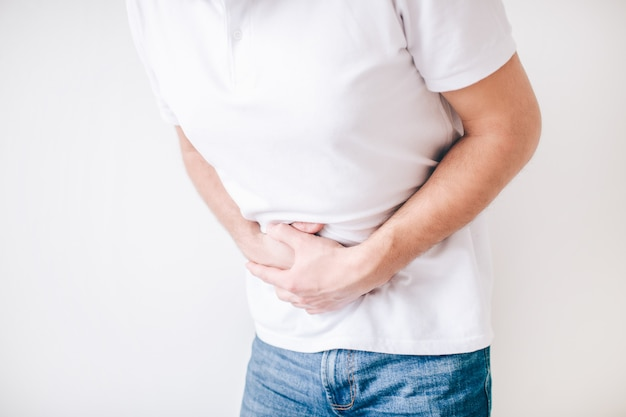 Young man isolated over white wall. cut view of guy holding hands over stomach because of diarrhea. painful and aching.
