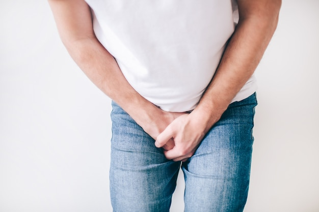 Young man isolated over white wall. cut view low part body. guy hold both hands on crotch. painful and terrible urine problem.