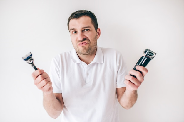 Young man isolated over white wall. guy confused with hard choice between shaving razor and shaving machine. hold them in hands.