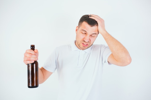 Young man isolated over white wall. guy suffers from headache and hangover. hold bottle in hand. suffer from pain.