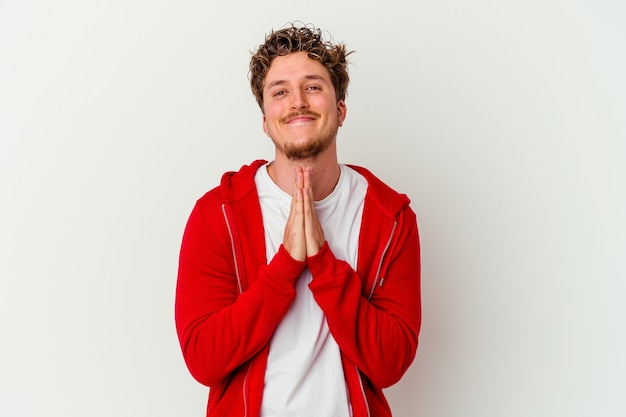 Young man isolated on white wall holding hands in pray near mouth, feels confident