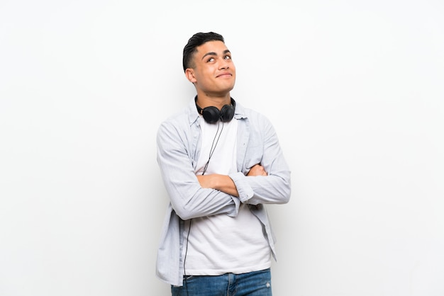 Young man isolated white wall with earphones looking up while smiling