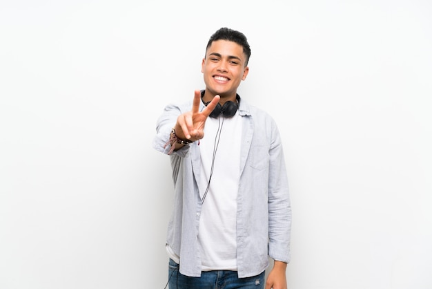 Young man over isolated white wall with earphones smiling and showing victory sign