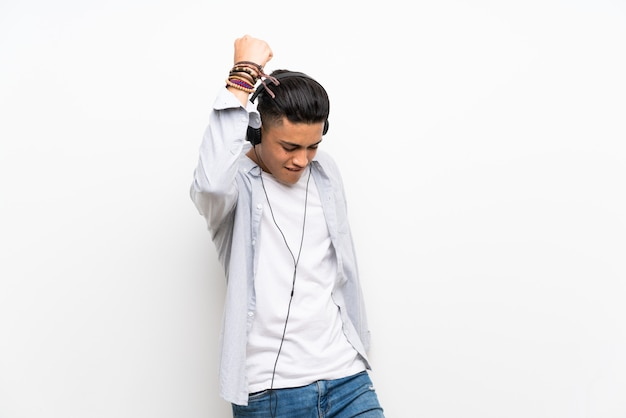 Young man over isolated white wall with earphones