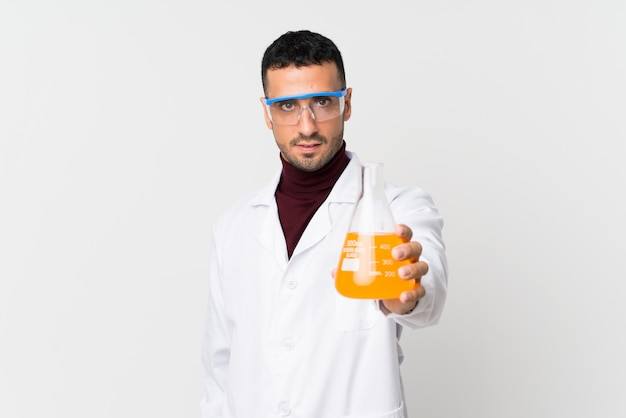 Young man over isolated white wall with a scientific test tube