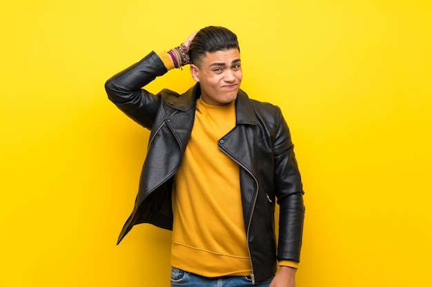 Young man over isolated yellow background having doubts while scratching head